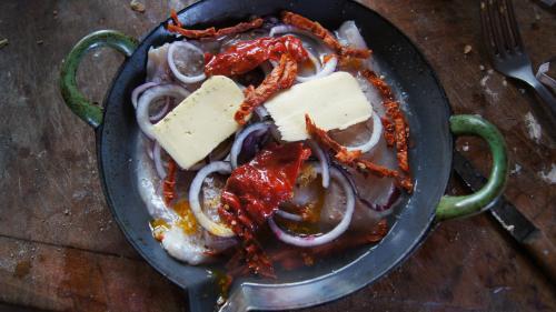 Filet de poisson, rondelles d'oignon, herbes, beurre frais, tomate séchée, poivron à l'huile